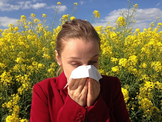 woman suffering hay fever in field of flowers